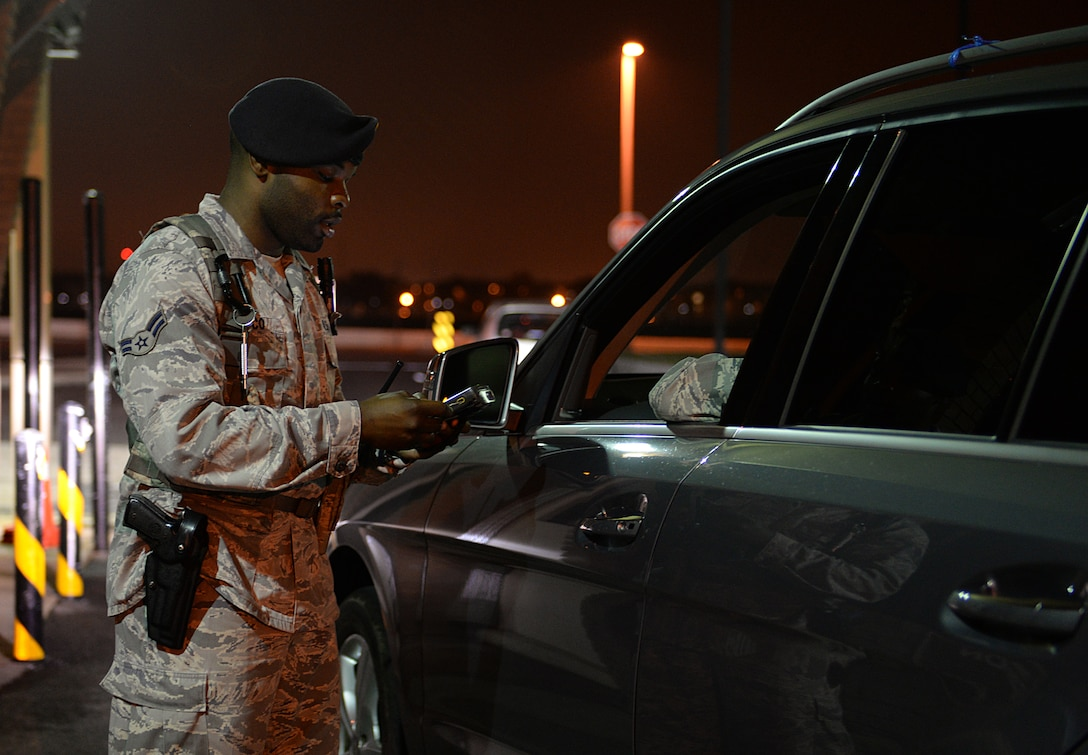 Airman 1st Class Darryl Glasco, 81st Security Forces entry controller, checks I.D. cards at a base entrance March 12, 2015, Keesler Air Force Base, Miss. 81st SFS Airmen perform multiple roles to keep members of Keesler safe, ranging from identification checks at base entrances to searching for explosives and narcotics with military working dogs. (U.S. Air Force photo by Senior Airman Holly Mansfield)
