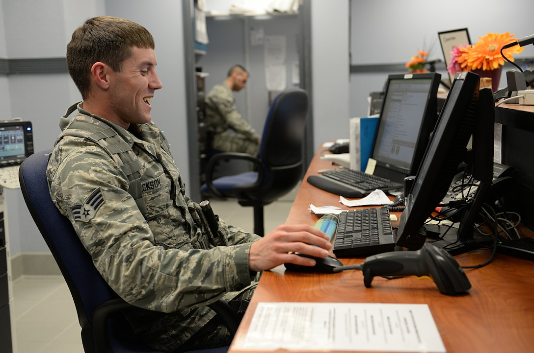 Senior Airman Danny Jackson, pass and identification shift supervisor, issues a temporary pass for a visitor March 12, 2015, Keesler Air Force Base, Miss. 81st SFS Airmen perform multiple roles to keep members of Keesler safe, ranging from identification checks at base entrances to searching for explosives and narcotics with military working dogs. (U.S. Air Force photo by Senior Airman Holly Mansfield)