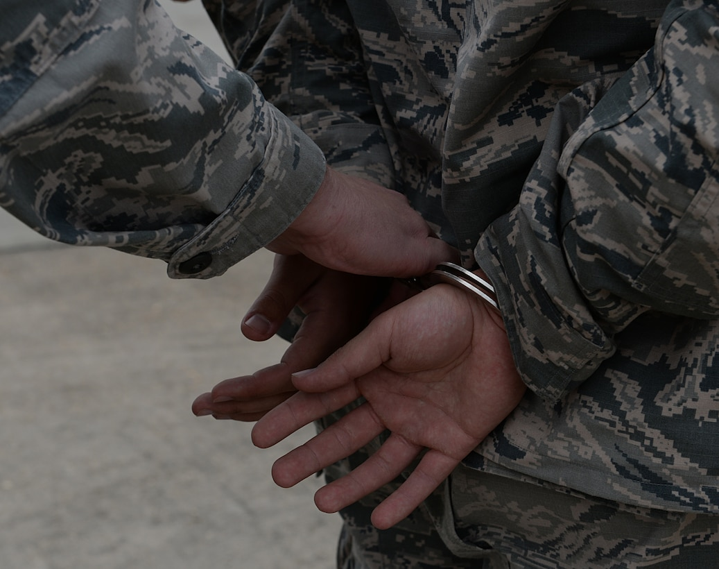 Airman 1st Class Britton Smith, 81st Security Forces internal security response team leader, simulates apprehending an Airman on the flightline March 12, 2015, Keesler Air Force Base, Miss. 81st SFS Airmen perform multiple roles to keep members of Keesler safe, ranging from identification checks at base entrances to searching for explosives and narcotics with military working dogs. (U.S. Air Force photo by Senior Airman Holly Mansfield)