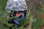 An airman reacts to sniper fire and incoming grenades while searching for assets during a training event at the Guardian Center in Perry, Ga., March 13, 2015. The exercise provides a refresher course for airmen, allowing them to use their skills to identify live chemical, biological, radiological and nuclear agents and materials.