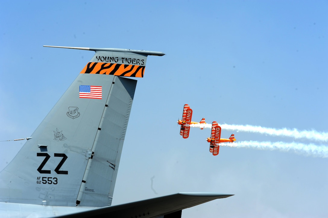 The U.K. stunt team, Breitling Wingwalkers, fly over a KC-135 Stratotanker during Aero India15, Feb. 19, 2015, at Air Force Station Yelahanka in Bengaluru, India. The KC-135 is from the 909th Air Refueling Squadron at Kadena Air Base, Japan. Aero India is India's premier aerospace exhibition and airshow and allowed the U.S. to demonstrate its commitment to the security of the Indo-Asia-Pacific region and showcase defense aircraft and equipment, which ultimately contributes toward better regional cooperation and tactical compatibility with other countries. This year marks the 10th iteration of Aero India since its inception in 1996. (U.S. Air Force photo/Airman 1st Class Stephen G.Eigel)