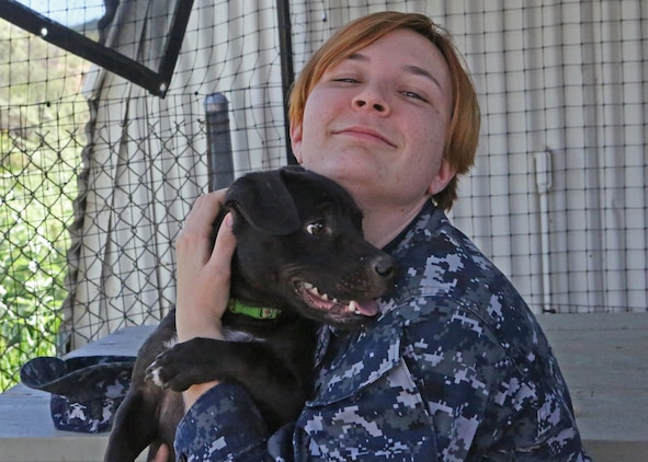 Petty Officer 3rd Class Mary Miller adopts a puppy during the St. Patrick's Day Lucky Adoption Event, March 14 at the Camp Pendleton Animal Shelter. With events like the St. Patrick's Day Lucky Adoption Event, the base shelter hopes to promote pet adoption by reducing normal adoption fees from $110 for dogs and $85 for cats to a cheaper amount which the adopters randomly draw from a hat. The fees are inclusive of neutering, a rabies vaccine, tracking microchip, a distemper vaccine and flea control.