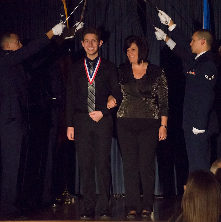 Nicholas Parkinson takes the stage with his mother Leila Parkinson during the Annual Awards ceremony at Mountain Home Air Force Base, Idaho, Feb. 18, 2015. Nicholas was recognized as the youth volunteer for the wing during the first and fourth quarter. (U.S. Air Force photo by Airman 1st Class Jessica H. Smith/RELEASED)