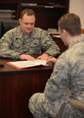 Airman 1st Class Matthew Gallagher, 28th MXS avionics test station technician, reviews his mobility folder with Master Sgt. Matthew Miller, 28th Maintenance Squadron unit deployment manager, at Ellsworth Air Force Base, S.D., March 4, 2015. UDMs ensure squadron personnel have necessary deployment items and inform leadership of the unit's deployment status. (U.S. Air Force photo by Airman 1st Class Rebecca Imwalle/Released)