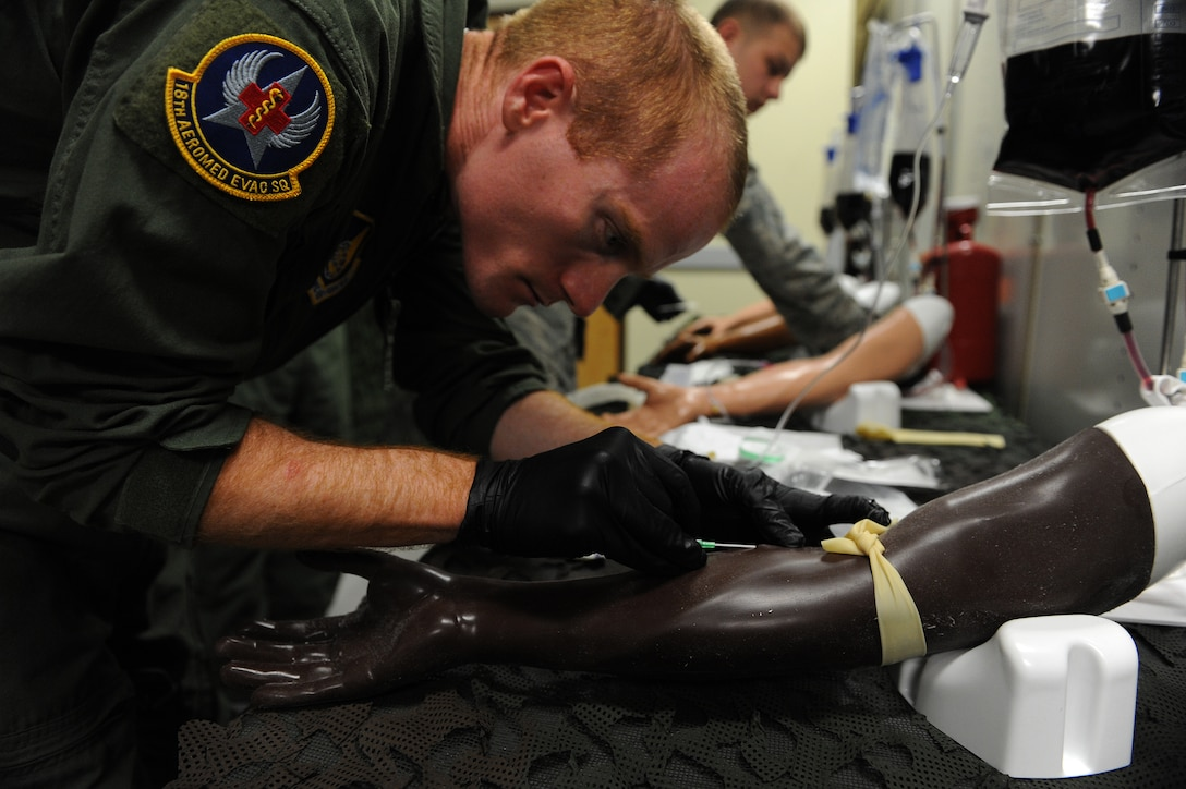 U.S. Air Force Staff Sgt. Joel Pallon, 18th Aeromedical Evacuation Squadron air evacuation medic, inserts a needle into a mannequin arm to practice intravenous therapy on Kadena Air Base, Japan, March 4, 2015. Intravenous therapy is one of the most common medical practices used to correct electrolyte imbalances, to deliver medications, for blood transfusion or fluid replacement. (U.S. Air Force photo by Airman 1st Class Stephen G. Eigel)
