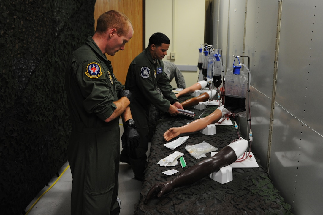 Members of the 18th Aeromedical Evacuation Squadron prepare to practice intravenous therapy on mannequin arms on Kadena Air Base, Japan, March 4, 2015. The 18th AES has recently built a one-of-a-kind training center that can be used for multiple medical services. (U.S. Air Force photo by Airman 1st Class Stephen G. Eigel)