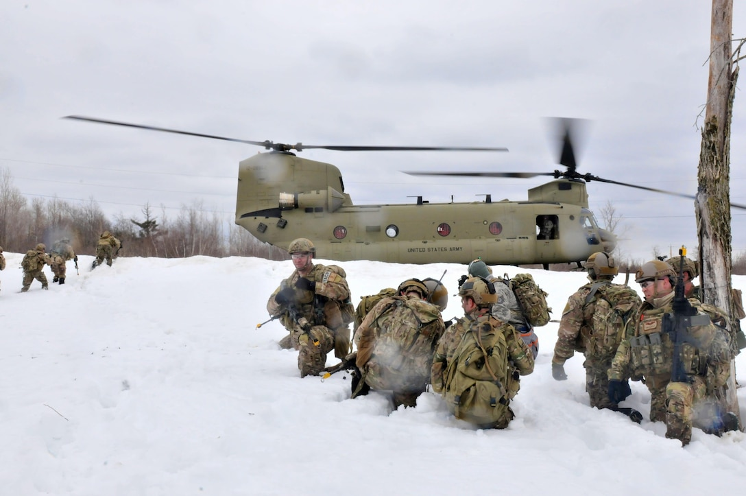 Airmen from the New York Air National Guard's 274th Air Support Operations Squadron wait to board a CH-47 F helicopter from Company B, 2nd Battalion, 126th Aviation of the New York Army National Guard during joint training March 14, 2015, at Fort Drum, N.Y. The two units teamed up to conduct air insertion and tactical training at Fort Drum. (New York Air National Guard photo/Master Sgt. Eric Miller)