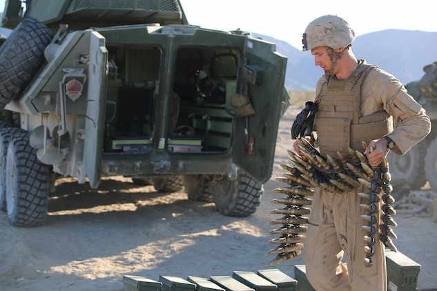 Cpl. Ryan Donk, vehicle commander, Light Armored Vehicle Platoon, Company B, Ground Combat Element Integrated Task Force, prepares to load 25mm Bushmaster chain gun rounds during a Marine Corps Operational Test and Evaluation Activity assessment at Range 500, Marine Corps Air Ground Combat Center Twentynine Palms, California, March 10, 2015. From October 2014 to July 2015, the GCEITF will conduct individual and collective level skills training in designated ground combat arms occupational specialties in order to facilitate the standards-based assessment of the physical performance of Marines in a simulated operating environment performing specific ground combat arms tasks. (U.S. Marine Corps photo by Cpl. Paul S. Martinez/Released)