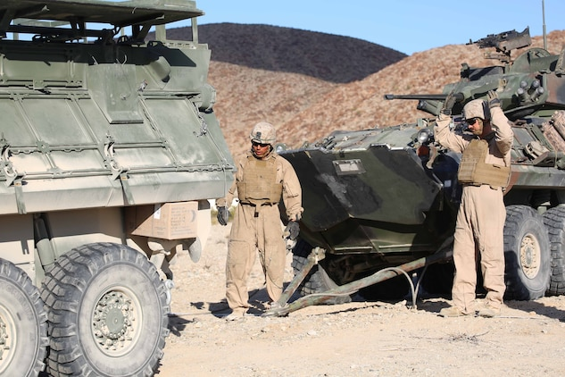 Cpl. Peteray C. Scantrach, right, gunner, Light Armored Vehicle Platoon, Company B, Ground Combat Element Integrated Task Force, directs an LAV during a Marine Corps Operational Test and Evaluation Activity assessment at Range 500, Marine Corps Air Ground Combat Center Twentynine Palms, California, March 12, 2015. From October 2014 to July 2015, the GCEITF will conduct individual and collective level skills training in designated ground combat arms occupational specialties in order to facilitate the standards-based assessment of the physical performance of Marines in a simulated operating environment performing specific ground combat arms tasks. (U.S. Marine Corps photo by Cpl. Paul S. Martinez/Released)