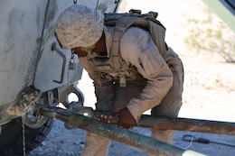 Cpl. Benjamin Alexander, vehicle commander, Light Armored Vehicle Platoon, Company B, Ground Combat Element Integrated Task Force, secures the towbar of an LAV during a Marine Corps Operational Test and Evaluation Activity assessment Range 500, Marine Corps Air Ground Combat Center Twentynine Palms, California, March 12, 2015. From October 2014 to July 2015, the GCEITF will conduct individual and collective level skills training in designated ground combat arms occupational specialties in order to facilitate the standards-based assessment of the physical performance of Marines in a simulated operating environment performing specific ground combat arms tasks. (U.S. Marine Corps photo by Cpl. Paul S. Martinez/Released)