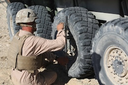 Cpl. Curtis Clifton, vehicle commander, Light Armored Vehicle Platoon, Company B, Ground Combat Element Integrated Task Force, secures the lug nuts of an LAV wheel during a Marine Corps Operational Test and Evaluation Activity assessment at Range 500, Marine Corps Air Ground Combat Center Twentynine Palms, California, March 12, 2015. From October 2014 to July 2015, the GCEITF will conduct individual and collective level skills training in designated ground combat arms occupational specialties in order to facilitate the standards-based assessment of the physical performance of Marines in a simulated operating environment performing specific ground combat arms tasks. (U.S. Marine Corps photo by Cpl. Paul S. Martinez/Released)