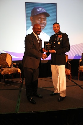 Marquis Grissom, an alumnus of Florida Agricultural and Mechanical University is presented with the Marine Corps Excellence in Leadership award by U.S. Marine Corps Lt. Col. Ricardo T. Player, the Marine Forces Command Director of Public Affairs, at the Mid-Eastern Athletic Conference Hall of Fame brunch in Norfolk, Virginia, March 13, 2015. The award recognizes the hard work and dedication of people who positively affect their communities. (U.S. Marine Corps Photo by Sgt. Nicholas S. Ranum/Released)