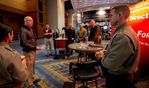 CDR Richard Newton (left) goes over the plan of the day before the show opens at the 2015 Naval Future Force Science and Technology Expo. CDR Newton and (left to right) Capt Angelica Valdez, TC Moore, Capt Brad Goldgvarg, LtCol Jody White, LtCol Patrick Kirchner, and LtCol Jeff Holt spent two days meeting with government and industry visitors at the expo to inform and educate them on the Futures Directorate and to also find potential solutions to the Marine Corps' S&T related needs.