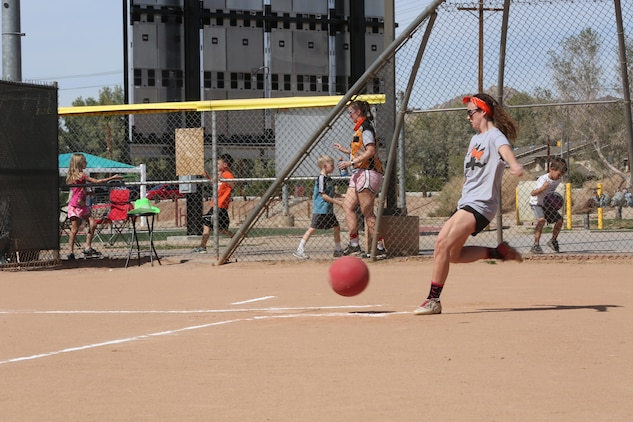 Julia Cramer, pitcher, the Lady Coyotes, kicks the ball during a spouses' kickball game at Felix Field, March 15, 2015. Cramer plays for the Lady Coyotes, which consists of spouses from the Marine Corps Tactical Training Exercise Control Group. (Official Marine Corps photo by Pfc. Levi Schultz/Released)
