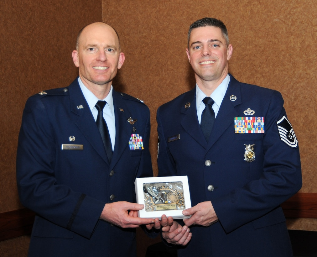 Oregon Air National Guard Col. Paul Fitzgerald, 142nd Fighter Wing commander, left, presents the Maj. Gen. Chester E. McCarty Award for General Support (142nd Fighter Wing level) to Master Sgt. Sean Penninger, assigned to the 142nd Civil Engineer Squadron, right, during the 21st Annual Oregon Air National Guard Awards Banquet, March 14, 2015, Portland, Ore. (U.S. Air National Guard photo by Tech. Sgt. Emily Thompson, 142nd Fighter Wing Public Affairs/Released)
