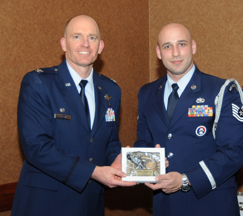 Oregon Air National Guard Col. Paul Fitzgerald, 142nd Fighter Wing commander, left, presents the 142nd Fighter Wing Honor Guard Member of the Year Award to Tech. Sgt. Justin Meininger, assigned to the 142nd Maintenance Group, right, during the 21st Annual Oregon Air National Guard Awards Banquet, March 14, 2015, Portland, Ore. (U.S. Air National Guard photo by Tech. Sgt. Emily Thompson, 142nd Fighter Wing Public Affairs/Released)