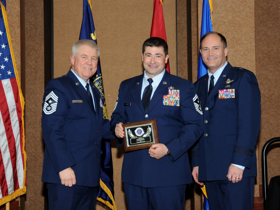 Oregon Air National Guard Senior Master Sgt. Brent Cavanias, assigned to the 125th Special Tactics Squadron, center, is presented with the overall Oregon Air National Guard First Sergeant of the Year  Award, from 173rd Fighter Wing Command Chief Master Sgt. Danny Ross, left, and Air Component Commander Brig. Gen. Michael Stencel, right, during the 21st Annual Oregon Air National Guard Awards Banquet, March 14, 2015, Portland, Ore. (U.S. Air National Guard photo by Tech. Sgt. Emily Thompson, 142nd Fighter Wing Public Affairs/Released)
