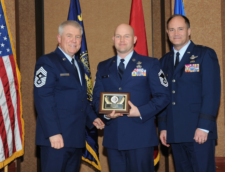 Oregon Air National Guard Senior Master Sgt. Jason Witts, assigned to the 173rd Logistical Readiness Squadron, center, is presented with the overall Oregon Air National Guard Outstanding Airman of the Year Award,  Category III, from 173rd Fighter Wing Command Chief Master Sgt. Danny Ross, left, and Air Component Commander Brig. Gen. Michael Stencel, right, during the 21st Annual Oregon Air National Guard Awards Banquet, March 14, 2015, Portland, Ore. (U.S. Air National Guard photo by Tech. Sgt. Emily Thompson, 142nd Fighter Wing Public Affairs/Released)