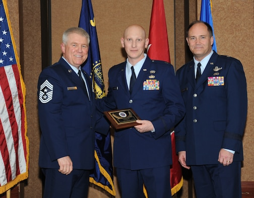 Oregon Air National Guard Capt. Jonathan Corrigan, assigned to the 142nd Civil Engineer Squadron, center, is presented with the overall Oregon Air National Guard Outstanding Company Grade Officer of the Year Award, from 173rd Fighter Wing Command Chief Master Sgt. Danny Ross, left, and Air Component Commander Brig. Gen. Michael Stencel, right, during the 21st Annual Oregon Air National Guard Awards Banquet, March 14, 2015, Portland, Ore. (U.S. Air National Guard photo by Tech. Sgt. Emily Thompson, 142nd Fighter Wing Public Affairs/Released)