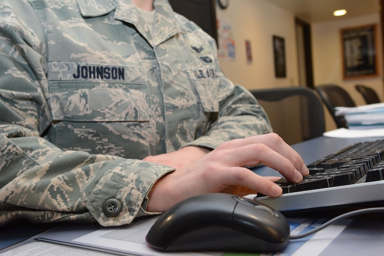 Staff Sgt. Chris Johnson, 115th Fighter Wing accounting liaison, uses the 10-key as he answers questions for Airmen at the 115 FW in Madison, Wis., Feb. 4, 2015. Johnson was recently named the 2014 Non-commissioned Officer of the Year for the state of Wisconsin. His outstanding Airman nomination packet was one of dozens reviewed by a panel of five chief master sergeants. (U.S. Air National Guard photo by Senior Airman Andrea F. Rhode)