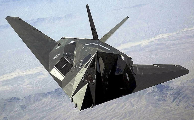 An F-117 Nighthawk flies over the Nevada desert. The unique design of the single-seat F-117 provides exceptional combat capabilities. The fighter can employ a variety of weapons and is equipped with sophisticated navigation and attack systems integrated into a digital avionics suite that increases mission effectiveness and reduces pilot workload. (U.S. Air Force photo/Staff Sgt. Aaron D. Allmon II)