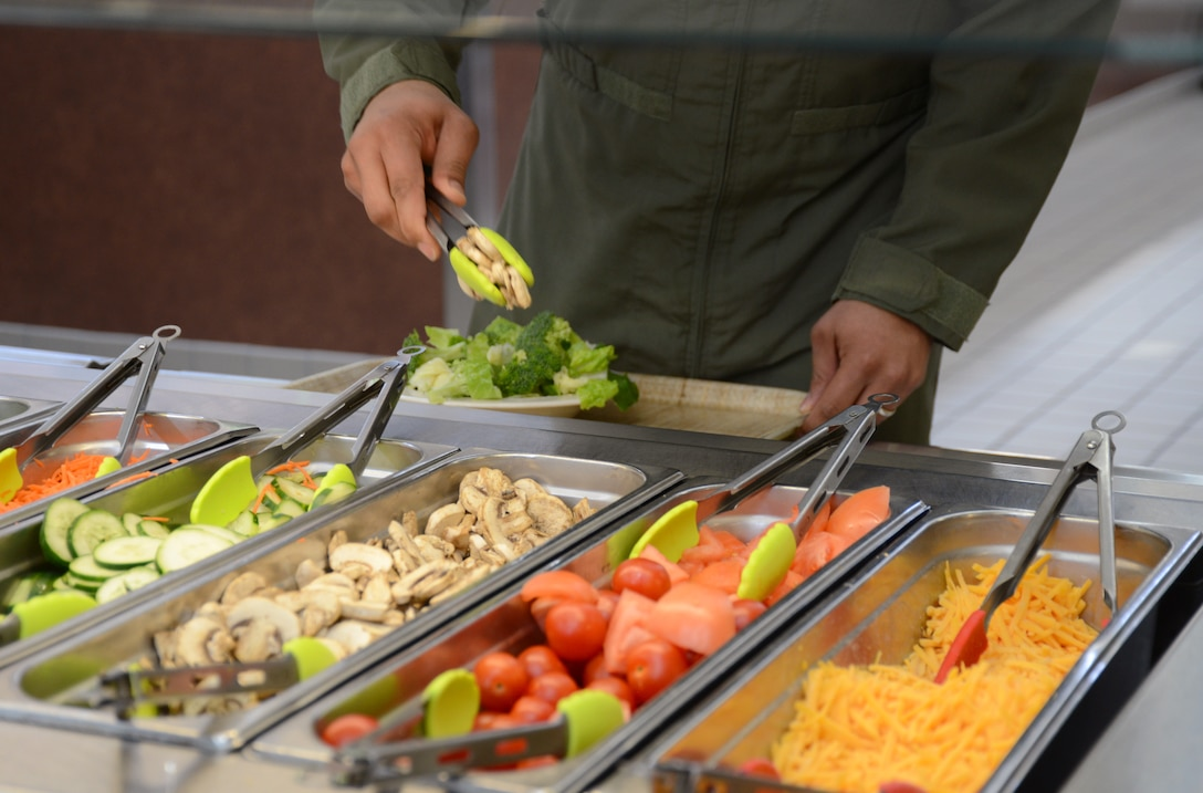 U.S. Air Force Tech. Sgt. Joey Wright of the 99th Airlift Squadron assembles a salad at Joint Base Andrews, Md., March 16, 2015, with tongs color coded according to the Go For Green program. Go For Green allows Airmen quickly make informed decisions about food choices, with the goal of supporting performance, readiness and resilience. (U.S. Air National Guard photo by Senior Airman John Hillier/Released)