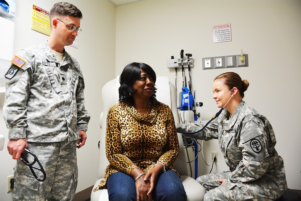 Army Maj. Marielos Vega listens to Sherry Moore's heart while Army Lt. Col. (Dr.) James Watts looks on in the cardiology department at Brooke Army Medical Center in San Antonio, March 17, 2015. U.S. Army photo by Robert T. Shields