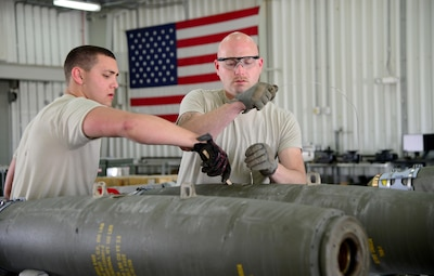Ammo Airmen assigned to the 379th Expeditionary Maintenance Squadron load a fuse into a guided bomb unit at Al Udeid Air Base, Qatar, March 13, 2015, at Al Udeid Air Base, Qatar. A GBU is a precision-guided munition designed to achieve greater accuracy.  For every individual munition expenditure made by the B-1, Ammo Airmen build one—which can mean they are building anywhere between six and 12 Joint Direct Attack Munitions at a time.  (U.S. Air Force photo by Senior Airman Kia Atkins)