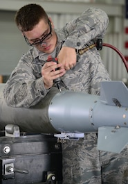 U.S. Air Force Airman 1st Class Kyle Newman, 379th Expeditionary Maintenance Squadron conventional maintenance crew member, attaches a fin to a guided bomb unit, March 13, 2015, at Al Udeid Air Base, Qatar. The fin is one of the final steps when completing the build of a GBU.  Ammo Airmen here at Al Udeid work 12 hours a day, seven days a week and provide 24 hour coverage to ensure the B-1s are always munitions ready when needed for airstrikes in support of Operation Inherent Resolve. (U.S. Air Force photo by Senior Airman Kia Atkins)