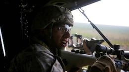Corporal David Elliot, a sniper with Bravo Company, 2nd Reconnaissance Battalion and a native of Santa Rosa, Calif., communicates with his partner during the aerial sniper portion of the machine-gun and aerial sniper familiarization exercise at training area SR-8 aboard Camp Lejeune, N.C., March 12, 2015. Marines with the unit used M240B machine guns and M110 semi-automatic sniper systems during the aerial sniper and machine gun familiarization fire.