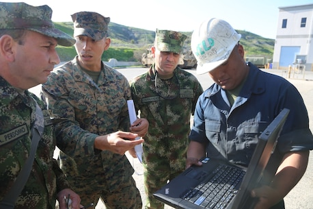 Sergeant Juan Arguello, center, an Engineer Equipment Mechanic with 1st Maintenance Battalion, Combat Logistics Regiment 15, 1st Marine Logistics Group, explains current computer software procedures to Lt. Col. Andres Perdomo, the Chief of Logistics for the Colombian Marine Corps, during a three-day tour around Combat Logistics Regiment 15, 1st Marine Logistics Group, aboard Camp Pendleton, California, March 3, 2015. Perdomo and Lt. Col. Ferdando Fernandez, a Battalion Commander for the Support Command, 6th Infantry Brigade, Colombian Marine Corps, visited 1st MLG to allow members of both the U.S. Marine Corps and Colombian Armed Forces to build an understanding of services, share best practices and strengthen camaraderie and interoperability. (U.S. Marine Corps photo by Sgt. Cody Haas/Released)