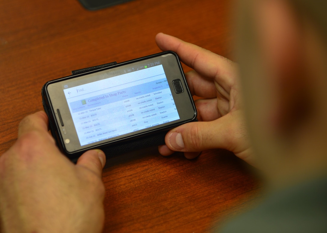 Tech. Sgt. Cory Cuadrado  views a Parts, Inspection, Turnover (PIT) log on his cellphone March 12, 2015, at Dover Air Force Base, Del. PIT was created by Staff Sgt. Chad Ericksen, 436th MXS NDI craftsman, to be a flexible yet accurate data recording program to replace outdated paper logs. Cuadrado is the non-destructive inspection NCO in charge assigned to the 436th Maintenance Squadron. (U.S. Air Force photo/Airman 1st Class William Johnson)