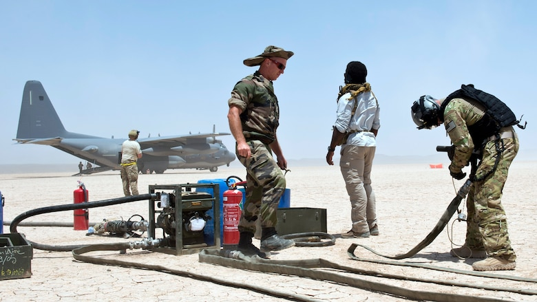 U.S. and French military members prepare fuel hoses from an HC-130 Combat King as part of a forward arming and refueling point exercise Mar 12, 2015, at Grand Bara, Djibouti . Providing a FARP allowed several smaller airframes to refuel with engines still running, enabling the aircrafts to fly missions almost non-stop. (U.S. Air Force photo/Staff Sgt. Kevin Iinuma)