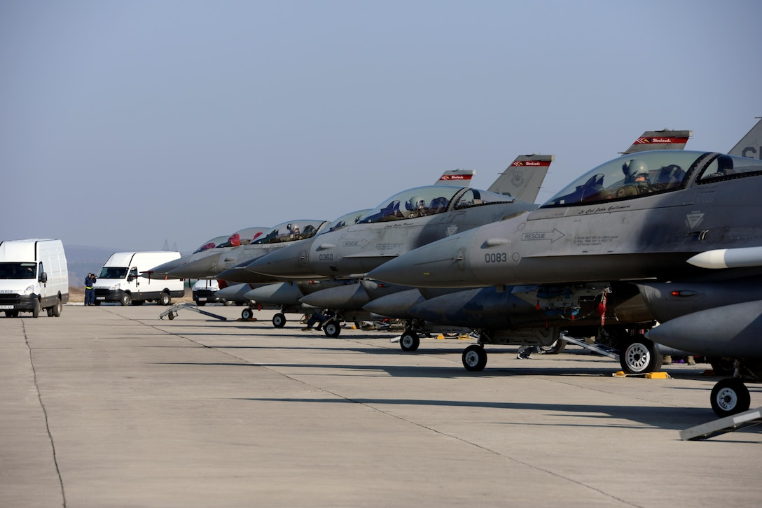 F-16CJ Fighting Falcons are lined up on the flightline for the first sortie of Dacian Warhawk, March 16, 2015, at Campia Turzii, Romania. Dacian Warhawk is a two-week long training mission designed to increase the interoperability between the U.S. and Romania. The training mission incorporated both ground and Air operations. The F-16s are assigned to the 480th Fighter Squadron. (U.S. Air Force photo/Staff Sgt. Kris Levasseur)