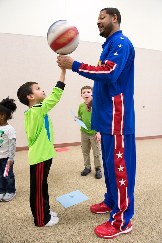 """Harlem Globetrotter Handles Franklin visits Illa School Age Program children on Joint Base Elmendorf-Richardson to discuss bullying prevention, March 17, 2015. Known worldwide as the """"Ambassadors of Goodwill""""™, the iconic Harlem Globetrotters presented the community outreach program, """"The ABCs of Bullying Prevention,"""" in an effort to impact schools and communities around the world as well as and provide tools that kids can use on a daily basis to reduce bullying. (U.S. Air Force photo/Alejandro Pena)"""