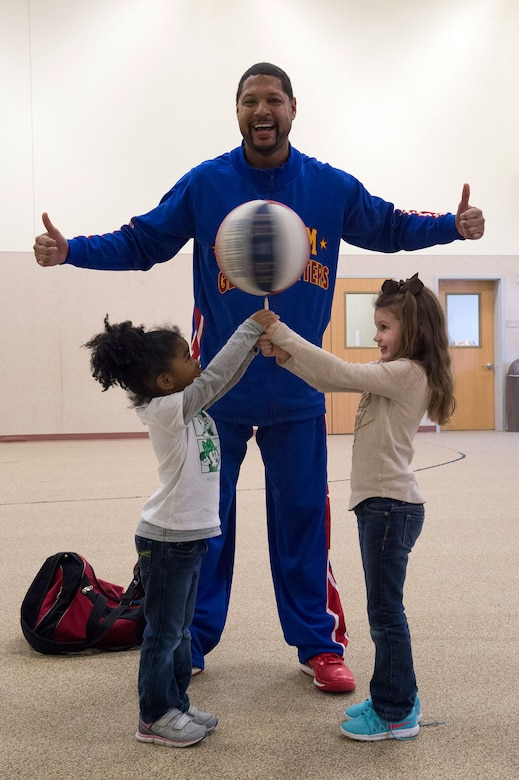"""Harlem Globetrotter Handles Franklin interacts with Dalainie Simon, 4, left, and Braelynne Ryan, 5, while visiting Illa School Age Program children on Joint Base Elmendorf-Richardson to discuss bullying prevention, March 17, 2015. Known worldwide as the """"Ambassadors of Goodwill""""™, the iconic Harlem Globetrotters presented the community outreach program, """"The ABCs of Bullying Prevention,"""" in an effort to impact schools and communities around the world as well as and provide tools that kids can use on a daily basis to reduce bullying. (U.S. Air Force photo/Alejandro Pena)"""