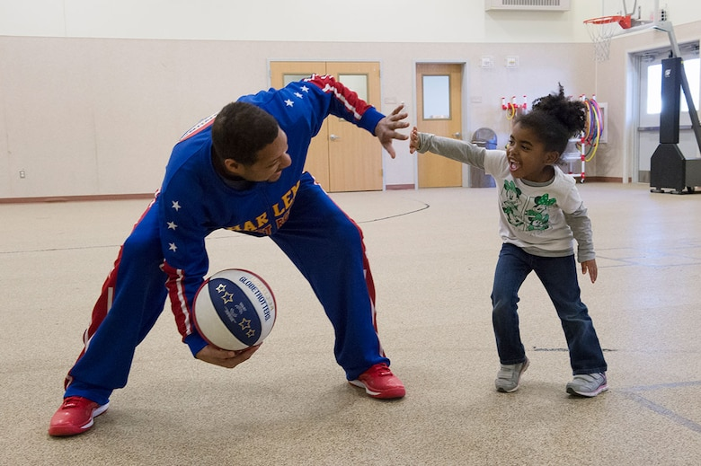 """Harlem Globetrotter Handles Franklin interacts with Delainie Simon, 4, while visiting Illa School Age Program children on Joint Base Elmendorf-Richardson to discuss bullying prevention, March 17, 2015. Known worldwide as the """"Ambassadors of Goodwill""""™, the iconic Harlem Globetrotters presented the community outreach program, """"The ABCs of Bullying Prevention,"""" in an effort to impact schools and communities around the world as well as and provide tools that kids can use on a daily basis to reduce bullying. (U.S. Air Force photo/Alejandro Pena)"""
