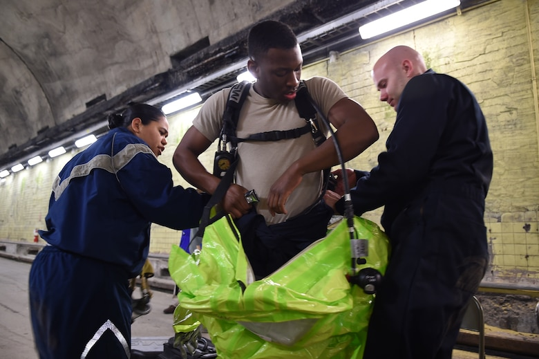 Senior Airman Tony Pauline (center), gets geared up for a chemical agent training exercise with help from Staff Sgt. Yaoska Quintana (left) and Staff Sgt. Jonathan Moroz (right) in the Memorial Tunnel at the Center for National Response in Gallagher, WV., March 17, 2015. All three Airmen are members of the 779th Aerospace Medical Squadron at Joint Base Andrews, Md. (U.S. Air Force photo/Airman 1st Class Joshua R. M. Dewberry)