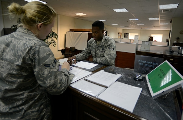 Airman 1st Class Robert Phillips III, 39th Security Forces Squadron Pass and Registration Section representative, assists a customer March 10, 2015, at Incirlik Air Base, Turkey. The American pass and registration office on base works with the Turkish pass and registration office for many different items concerning base access including friend and family gate passes for visiting. (U.S. Air Force photo by Staff Sgt. Caleb Pierce/Released)