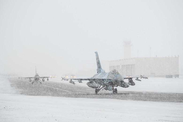 F-16 Fighting Falcons taxi down the runway March 3, 2015, at Eielson Air Force Base, Alaska. The F-16s are assigned to the 18th Aggressor Squadron. Aggressor pilots returned after completing a mobile training team exercise. (U.S. Air Force photo/Senior Airman Peter Reft)