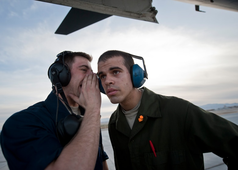 Airman 1st Class Gabriel Henry yells to Airman 1st Class Brian Allen during Red Flag 15-2 March 10, 2015, at Nellis Air Force Base, Nev. Any personnel located in the area of an aircraft with an engine on must wear hearing protection among other personal protective equipment. Both Airmen are crew chiefs assigned to the 28th Aircraft Maintenance Squadron at Ellsworth AFB, S.D. (U.S. Air Force photo/Staff Sgt. Siuta B. Ika)