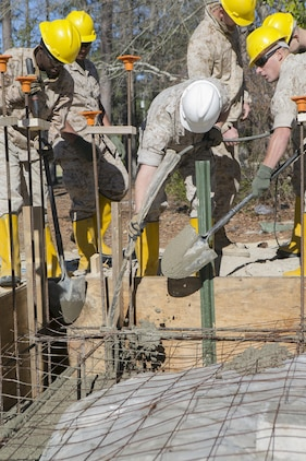 "Combat engineers with 8th Engineer Support Battalion, 2nd Marine Logistics Group, use shovels and a concrete vibrator to evenly distribute and remove air pockets from concrete March 18, 2015, aboard Camp Lejeune, North Carolina. ""We're getting ready to deploy, and the way we're doing this project mirrors the way that we're going to be building the schools there,"" said Sgt. Christopher Panko, a combat engineer with the unit. ""It's giving the Marines good training on the process of what it takes to build from the ground up. As engineers, we normally focus on demolition. The past few years we haven't done a lot of construction projects, and the Marines haven't had a chance to do humanitarian work. This is a good opportunity, and with their experience level they're doing very well."" (U.S. Marine Corps photo by Cpl. Elizabeth A. Case/Released)"