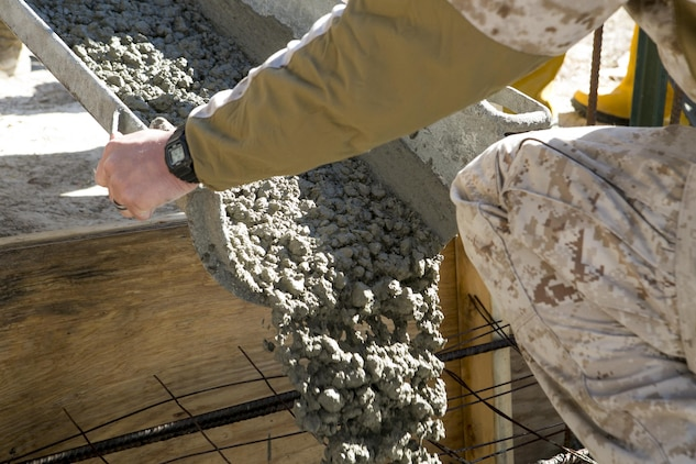 Sgt. Joshua Davis, a combat engineer with 8th Engineer Support Battalion, 2nd Marine Logistics Group and a Philadelphia, Pennsylvania, native, pours concrete at a construction site March 18, 2015, aboard Camp Lejeune, North Carolina, to establish the foundation for a storage facility. Upon completion, the building will be used to store the unit's martial arts equipment. Construction skills used in the project are preparing the Marines for an upcoming deployment, on which the engineers will use similar techniques to build schools and other structures. (U.S. Marine Corps photo by Cpl. Elizabeth A. Case/Released)