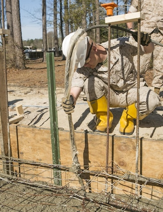 Cpl. Austin Gibson, a combat engineer with 8th Engineer Support Battalion, 2nd Marine Logistics Group and a Branson, Missouri, native, uses a concrete vibrator to remove air pockets from concrete March 18, 2015, aboard Camp Lejeune, North Carolina. Engineers with the unit are working to construct a storage facility for the unit's martial arts equipment. Construction skills used in the project are preparing the Marines for an upcoming deployment, in which the engineers will use similar techniques to build schools and other structures during humanitarian projects. (U.S. Marine Corps photo by Cpl. Elizabeth A. Case/Released)