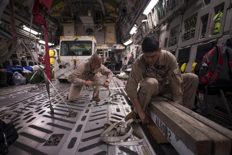 Marines assigned to Marine Corps Base Hawaii offload equipment from the back of a C-17 Globemaster III in preparation of the Langkawi International Maritime and Aerospace Exhibition March 16, 2015, in Langkawi, Malaysia. Defense Department participation in the LIMA 15 airshow strengthens military-to-military relationships and underscores the cooperation agreements between the U.S. and Malaysia. (U.S. Air Force photo/1st Lt. Elias Zani)