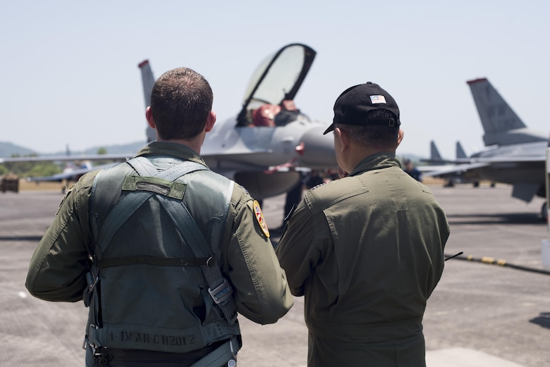 Capt. Austin Brown reviews his F-16 Fighting Falcon demonstration with a member of the Langkawi International Maritime and Aerospace Exhibition crew March 16, 2015, in Langkawi, Malaysia. Brown is a pilot assigned to the Pacific Air Forces demonstration team. Defense Department participation in the LIMA 15 airshow strengthens military-to-military relationships and underscores the cooperation agreements between the U.S. and Malaysia. (U.S. Air Force photo/1st Lt. Elias Zani)
