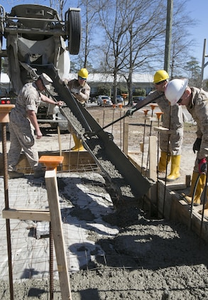 "Combat engineers with 8th Engineer Support Battalion, 2nd Marine Logistics Group, use tools to pour concrete into a foundation, March 18, 2015, aboard Camp Lejeune, North Carolina. Upon completion, this building will be a storage facility for the unit's martial arts equipment. ""We're getting ready to deploy, and the way we're doing this project mirrors the way that we're going to be building the schools there,"" said Sgt. Christopher Panko, a combat engineer with the unit. ""It's giving the Marines good training on the process of what it takes to build from the ground up. As engineers, we normally focus on demolition. The past few years we haven't done a lot of construction projects, and the Marines haven't had a chance to do humanitarian work. This is a good opportunity, and with their experience level they're doing very well.""  (U.S. Marine Corps photo by Cpl. Elizabeth A. Case/Released)"