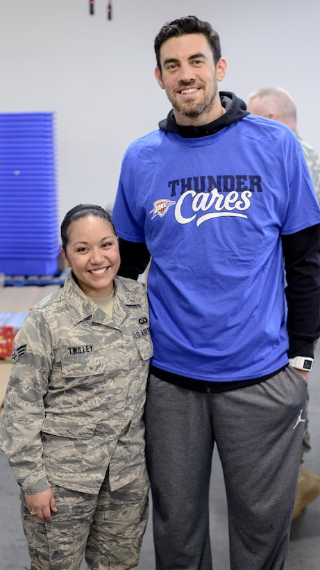 Senior Airman Susana Twilley poses with Oklahoma City Thunder's Nick Collison at the Regional Food Bank of Oklahoma, March 9, 2015. Team Vance partnered with area troops and Thunder basketball players for an NBA Cares and DOD volunteer outing. (U.S. Air Force photo by David Poe)