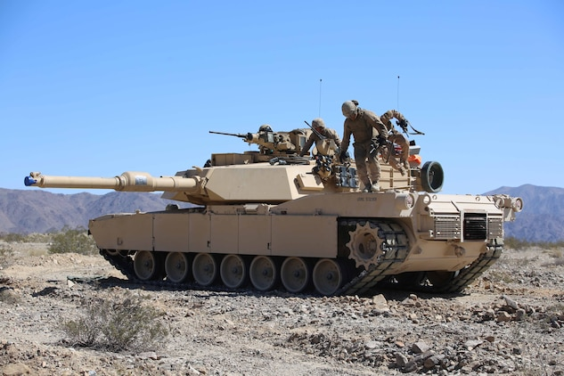 Marines with Tank Platoon, Company B, Ground Combat Element Integrated Task Force, conduct a crew evacuation drill off of an M1A1 Abrams tank during a Marine Corps Operational Test and Evaluation Activity assessment at Range 500, Marine Corps Air Ground Combat Center Twentynine Palms, California, March 7, 2015. From October 2014 to July 2015, the GCEITF will conduct individual and collective level skills training in designated ground combat arms occupational specialties in order to facilitate the standards-based assessment of the physical performance of Marines in a simulated operating environment performing specific ground combat arms tasks. (U.S. Marine Corps photo by Cpl. Paul S. Martinez/Released)