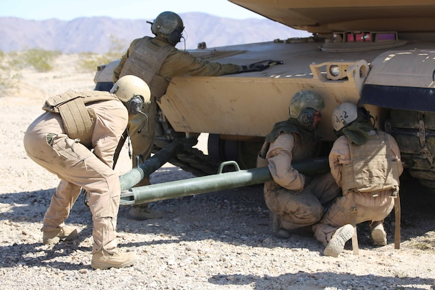 Marines with Tank Platoon, Company B, Ground Combat Element Integrated Task Force, conduct the towing of an M1A1 Abrams tank during a Marine Corps Operational Test and Evaluation Activity assessment at Range 500, Marine Corps Air Ground Combat Center Twentynine Palms, California, March 7, 2015. From October 2014 to July 2015, the GCEITF will conduct individual and collective level skills training in designated ground combat arms occupational specialties in order to facilitate the standards-based assessment of the physical performance of Marines in a simulated operating environment performing specific ground combat arms tasks. (U.S. Marine Corps photo by Cpl. Paul S. Martinez/Released)